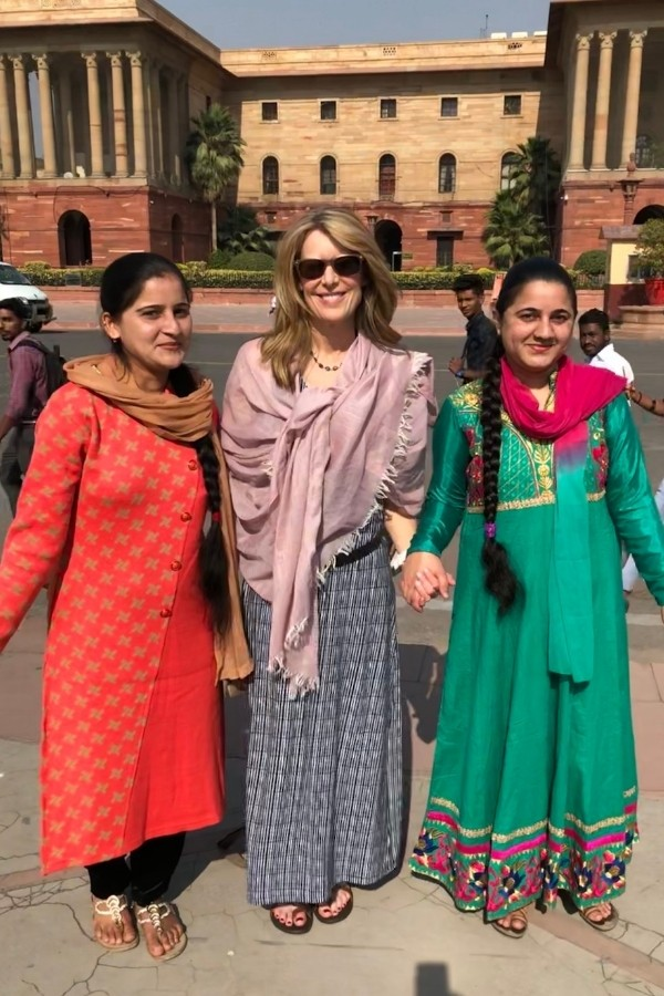Susan Heinrich holds hands with two women in Delhi India
