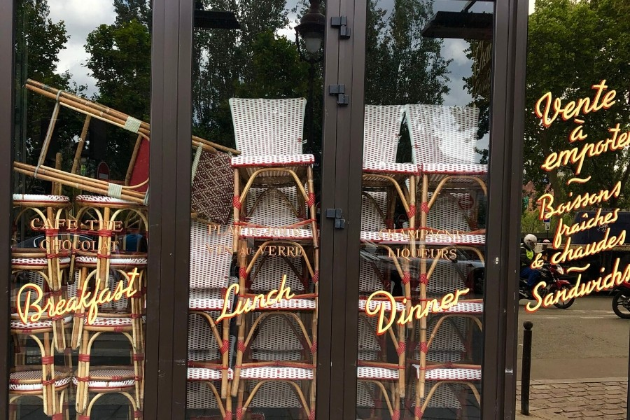Cafe chairs are stacked in a window in Paris