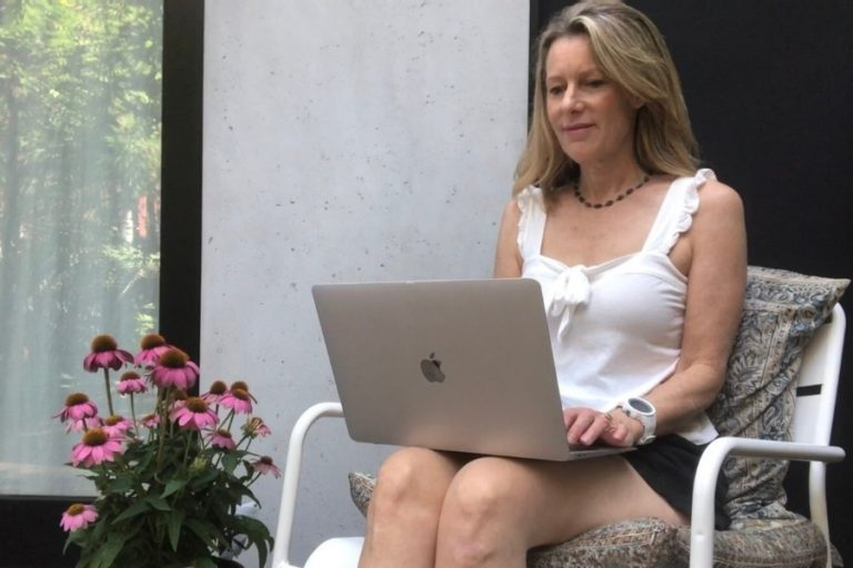 Susan Heinrich writing on a laptop with pink flowers next to her