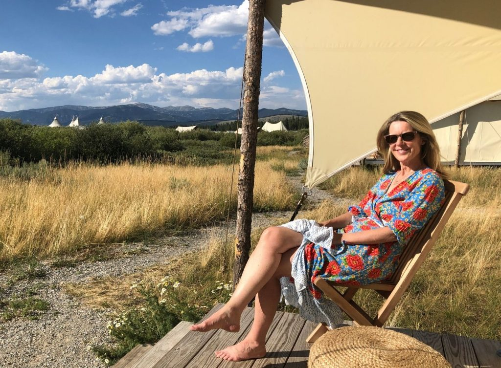 Susan Heinrich sits on the deck of a tent at near Yellowstone National Park in Montana